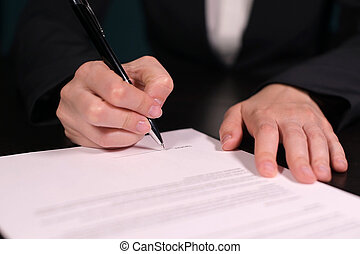 Woman signs a contract, close-up of hands with pen on paper