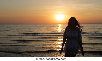 woman silhouette dancing and jumping on sunset beach