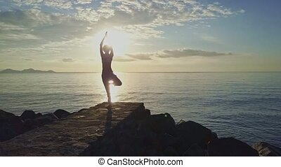 Woman Silhouette Does Yoga against Rising Sun above Ocean -...