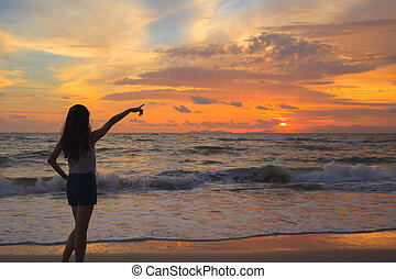 woman silhouette in the sunset and pointing