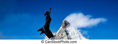 woman silhouette jumping against mountain peak