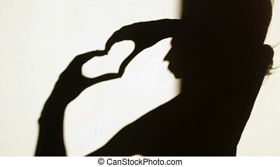 Woman silhouette showing heart with her hands. Love concept