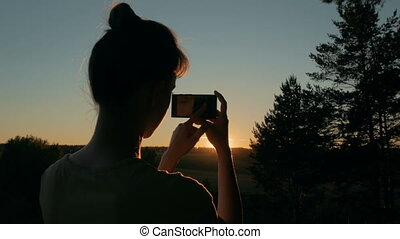Woman silhouette taking photo of amazing sunset with smartphone in park