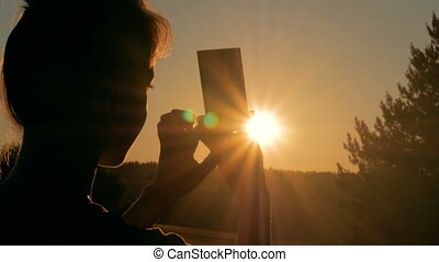 Woman silhouette taking photo of sunset with smartphone -...