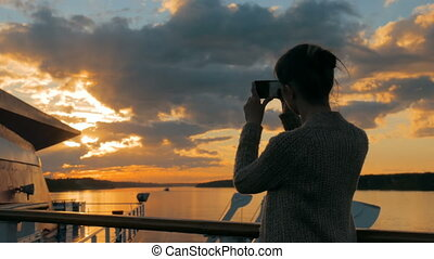 Woman silhouette taking photo of sunset with smartphone on...