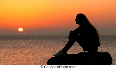 Woman silhouette watching sun at sunrise - Side view of a...