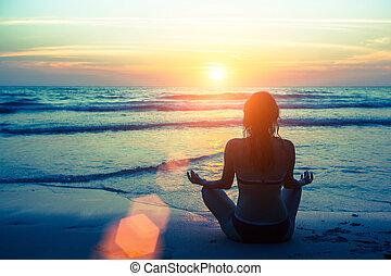 Woman silhouette yoga on the beach