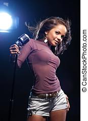 Woman singer in black background