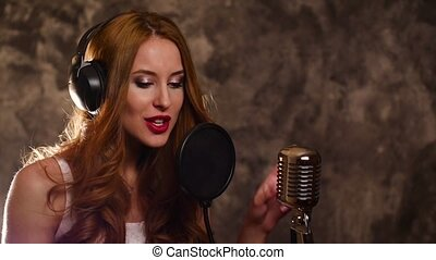 woman singer recording a song in music studio,slow motion, close up