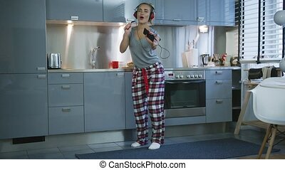 Woman singing and dancing in kitchen - Lovely woman in...