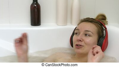 Woman singing in bath - Woman relaxing in bath at her home...