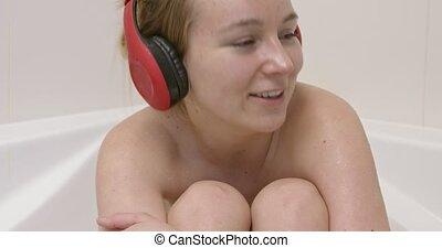 Woman singing in bath - Woman sitting in bath with...