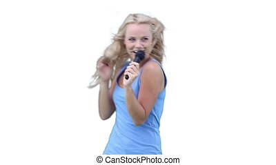 Woman singing into a microphone while dancing