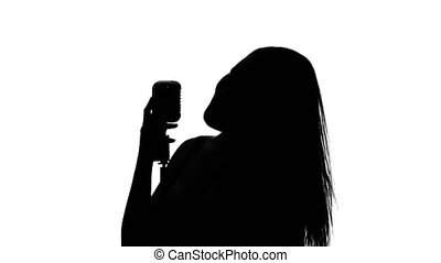 Woman sings a song and waves his hair. Close up. Silhouette. White