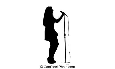 Woman sings incendiary songs into the microphone. White background. Silhouette. Slow motion