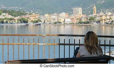 woman sit bench city sea bay skyline back view Rapallo...