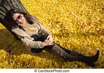 woman sit on ground be filled with leaves of the ginkgo tree in fall at japan