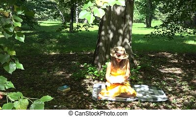 woman sit on plaid and read book in park under tree shadow. 4K