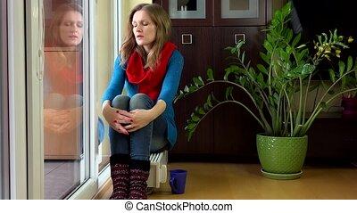 woman sit on radiator near window with cup tea living room. 4K