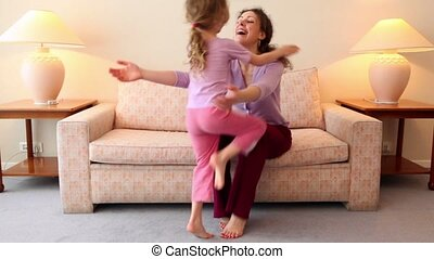 woman sit on sofa and catches her daughter runs to room with lamp on each side