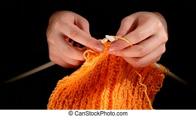 Woman sits and knits orange scarf, large knit on black...
