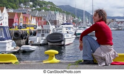 Woman sits and sings on quay in dock at coastal Bergen town...