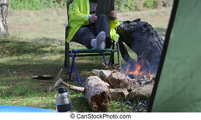 Woman sits at the campfire with tablet computer
