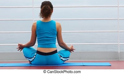 woman sits back on ship deck in lotus pose - woman in blue...