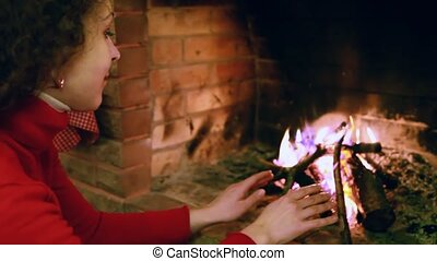 Woman sits by fire warming his hands