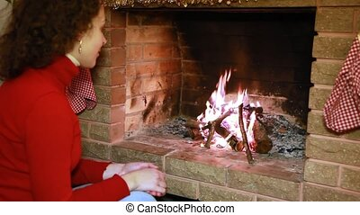 Woman sits by fireplace watch fire
