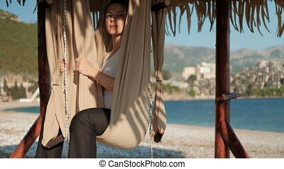 Woman sits in a hammock on a sunny beach and looks into the distance.