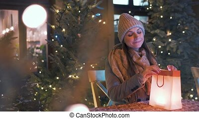 Woman sits in an outdoor cafe terrace in winter and looks in...