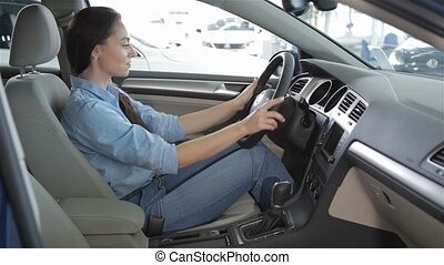 Woman sits inside the car at the dealership - Young...