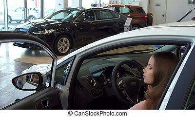 Woman sits into the car at the dealership