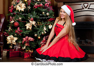 Woman sits near a Christmas tree