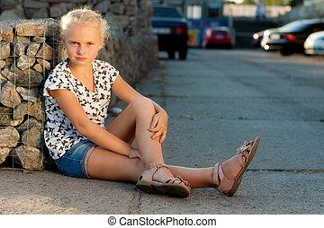 woman sits near a wall on the pavement