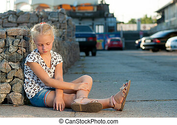 woman sits near a wall on the pavement