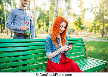 Woman sits on a bench, man with rose stands behind