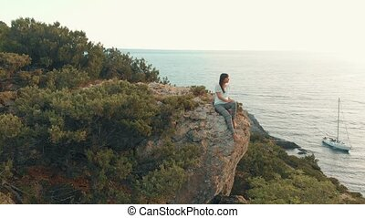 Woman sits on a boulder and watches seascape - Aerial view...