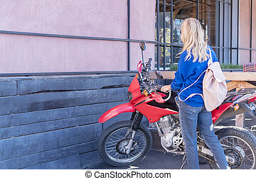woman sits on a motorcycle