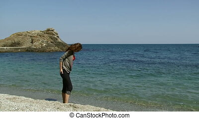 Woman sits on a rocky beach