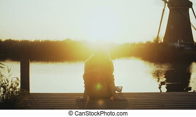 Woman sits on a small lake pier, watching sunset. Golden...