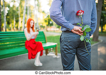 Woman sits on bench, man with rose stands against