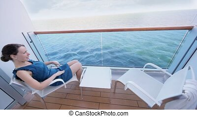 woman sits on chair before table in fenced part of deck of ship