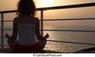 woman sits on deckchair on deck of cruise ship - woman sits...