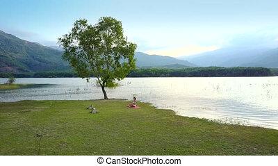 woman sits on green lake bank near large tree