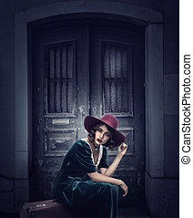Woman sits on suitcase, vintage style fashion