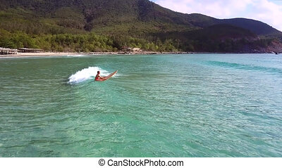 woman sits on surfboard sailing in ocean against hills -...