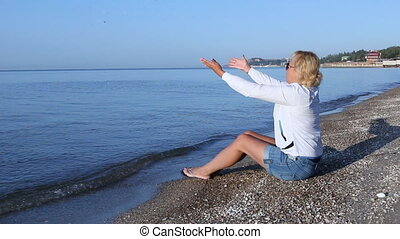 Woman sits on the beach of the Azov Sea and throwing stones into the water.