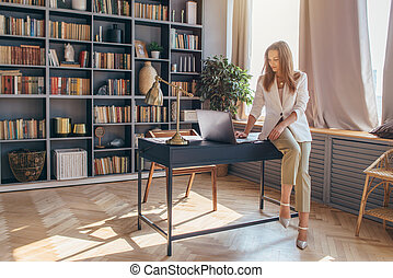 Woman sits on the edge of the desk and uses a laptop.